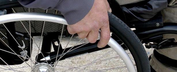 dettaglio di mano poggiata sulla ruota di una sedia a rotelle