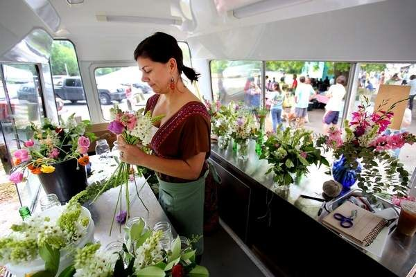 Toni Reale arranges flowers inside Ramblin' Rosie, a 1970s-era English ice-cream truck with all locally grown flowers at the Sunday Brunch Farmers Market on James Island.