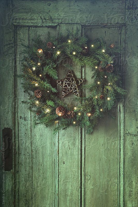 Holiday wreath on old wooden door by Sandra Cunningham