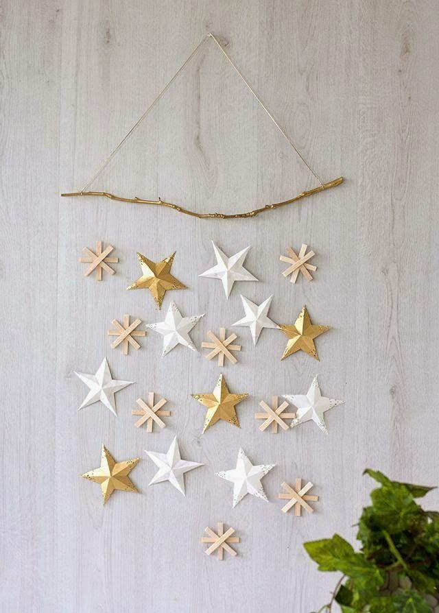 A l'aide de plusieurs bouts de ficelle et d'une branche repeinte en doré, suspendez des étoiles en papier et en bois que vous aurez confectionnées vous-mêmes. Vous pouvez aussi y suspendre des décorations ou boules de Noël achetées en magasin.