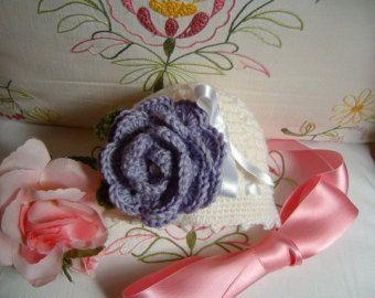 Cappellino per neonata eseguito a mano all'uncinetto in lana bianca con una rosa viola applicata. Crochet moda bebè romantica e femminile