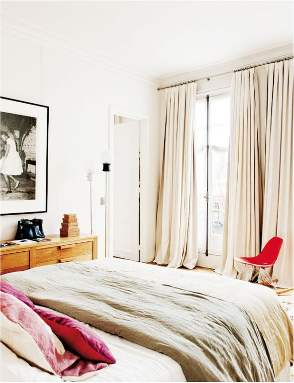 Neutral bedroom with one modern red chair