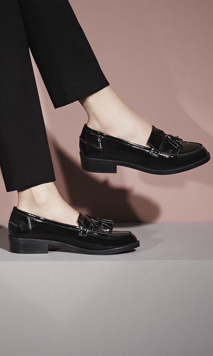 Classic tassels swing across the toe of a sleek, menswear-inspired loafer upgraded in glossy patent.