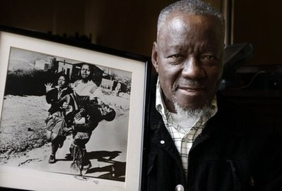 The Power of Photography: photographer Sam Nzima receives long overdue award from South African President Jacob Zuma.  He poses here with his iconic photograph that shows Hector Pieterson, a 13-year-old boy shot by police during the 1976 Soweto uprising.