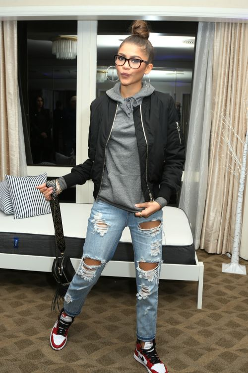 Fashion By Zendaya. Grey hoodie, ripped jeans, black jacket, black tennis shoes, topknot, glasses, silver hoops