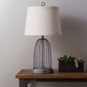 • Metal and resin<br>• Inspired by vintage cloche made of bird/chicken wire cage<br><br>The Baiter Table Lamp in Grey Wire from Beekman 1802 FarmHouse was inspired by that versatile material from the farm. The chicken wire lamp has classic appeal but fits marvelously in a modern setting.