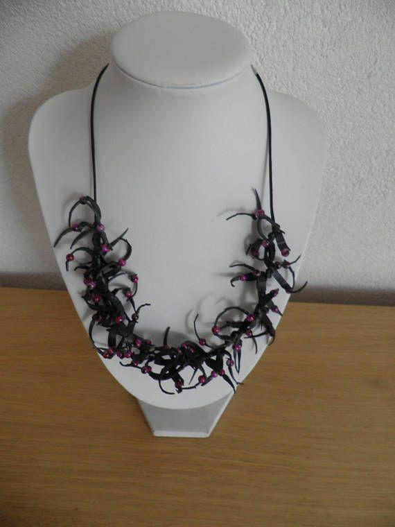 Ketting van zwart rubber met paarse kraaltjes en iets zwart op