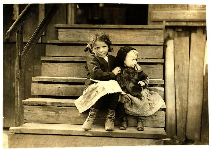 Little Julia tending the baby at home. All the older ones are at the factory. She shucks also. Alabama Canning Co.,. Location: Bayou La Batre, Alabama. Photograph by Lewis Wickes Hine, February 1911.