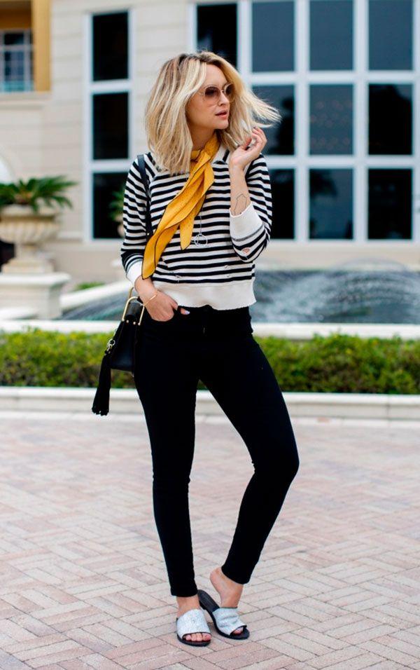Street style look com calça preta e blusa listras, lenço amarelo no pescoço e chinelo metalizado