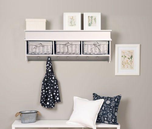 Mensola appendiabiti in legno bianco, con sette ganci e tre cestini in vimini foderati in tessuto. Perfetta per organizzare gli spazi.