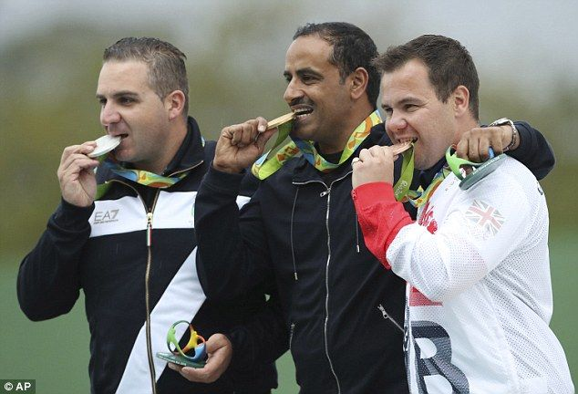 Gold medalist Fehaid Aldeehani, center, is flanked by silver medalist Marco Innocenti, left, of Italy and Steven Scott, right, of Britain during the award ceremony for the men's double trap