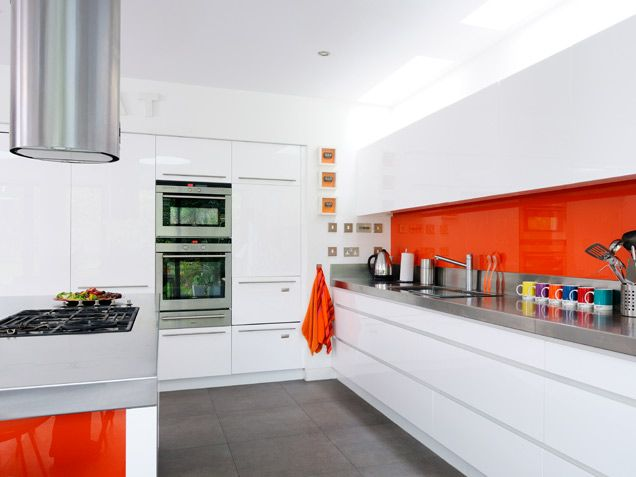 A shiny orange backsplash pops against a sleek mix of stainless steel and white lacquer -- #kitchens #decor #backsplash