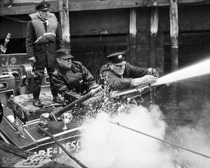 "FDNY firefighters test a shallow draft boat on Pier A in Manhattan. The negatives read that the tests were ""N.G."" Photo taken Jan. 11, 1961."