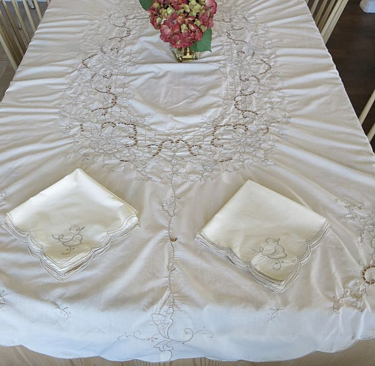 This is a large cream color oval tablecloth that has machined embroidery with ecru thread and lots of areas of open work. There are eight matching napkins. This tablecloth would look lovely with a darker tablecloth underneath accentuating the open areas of embroidery. It is from the 1970s-80s time frame and is made of a poly cotton fabric. There are no tags. The scalloped edges have been machine edged.  The oval tablecloth measures 84 inches by 68 inches. The napkins are approximately 16…
