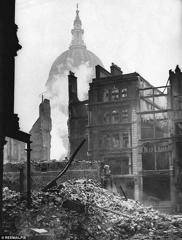 London's burning: Ruins of a building in the shadow of St Pauls still smoulder a week after the Blitz on the city in December 1940.