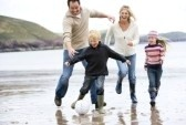 Family playing soccer at beach.
