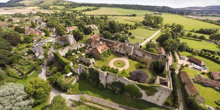 Amberley Castle Amberley, United Kingdom grass sky outdoor bird's eye view aerial photography Town residential area human settlement Village field hill tourism Ruins rural area green plant landscape Garden lush monastery château valley grassy mansion hillside pasture highland