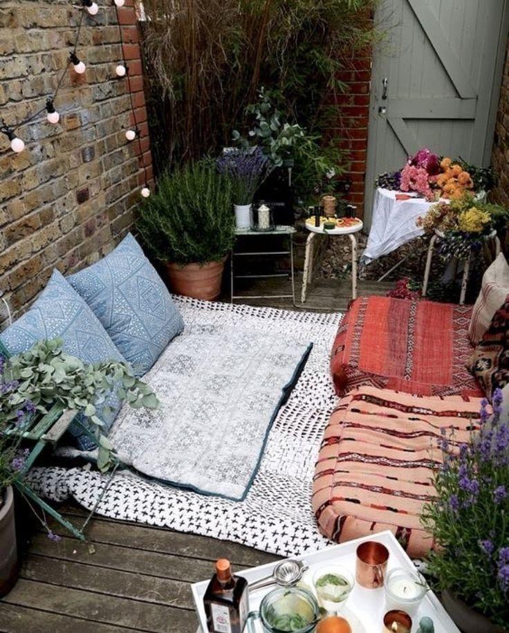 Coin cosy improvisé sur la petite terrasse guirlande lumineuse tabourets et coussins colorés