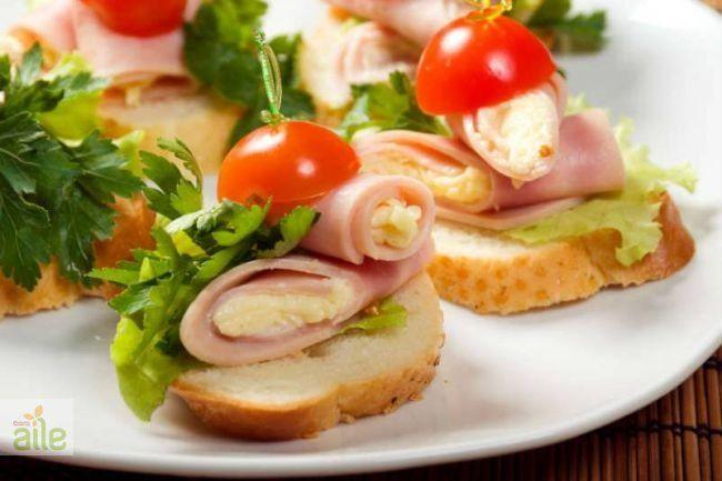 2,5 yemek kaşığı tereyağı 3 yemek kaşığı krem peynir 6 adet hindi jambon 6 adet çeri domates 6 adet beyaz tost ekmeği Hindi jambonlu kanepe tarifi hazırlanışı: Yuvarlak kestiğiniz sandviç ekmeklerine tereyağı sürün. Mayonez ile krem peynirini karıştırıp, ekmekleri kaplayın. Hindi jambonu yerleştirin. Çeri domatesle süsleyin.