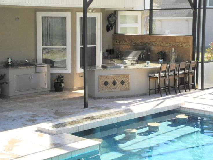 Outdoor kitchen with swim up bar.  Outdoor kitchen designed and constructed by Creative Design Space Fleming Island, FL.