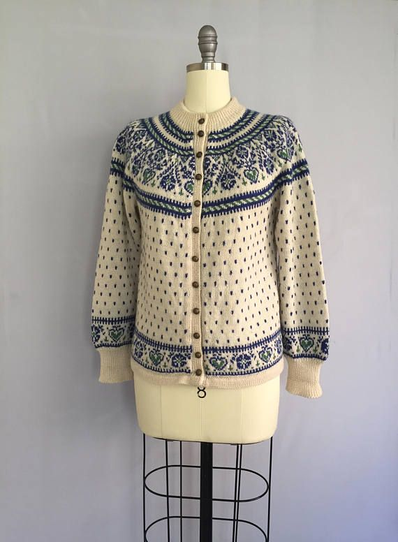 A lovely fairisle cardigan from the 1950s The cardigan has been hand knitted from super soft wool with a traditional Norwegian folk pattern around the neck and sleeve cuffs in shades of forest green and royal blue on a cream background. The knit has long sleeves with ribbed sleeve
