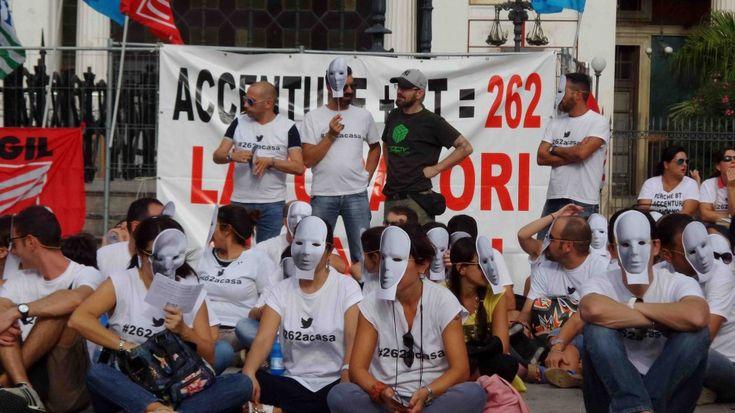 """Manifestazione di protesta degli operatori del call center Accenture di Palermo. Un sit-in e' in corso in piazza Ruggero Settimo, davanti il teatro Politeama. Sono 262 i lavoratori a rischio licenziamento. I manifestanti, con il volto coperto, indossano maschere bianche: """"Per le aziende - lamentano - siamo senza volto! Vergognatevi, siamo solo numeri, per questo oggi abbiamo indossato le maschere. Vengono ignorati i nostri diritti e le professionalita' acquisite"""". Cosi' in piazza Ruggero ..."""