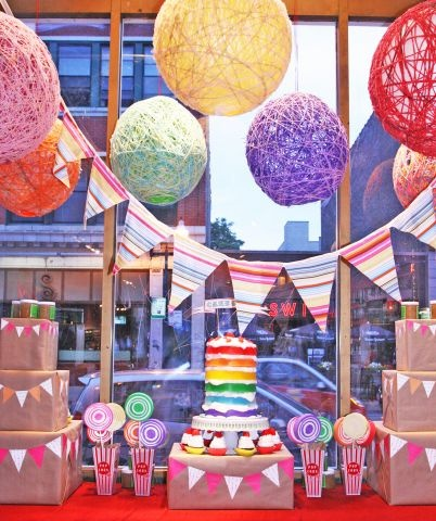 Mojo Spa's window display in Chicago, rainbow tiered cake soap and yarn lanterns