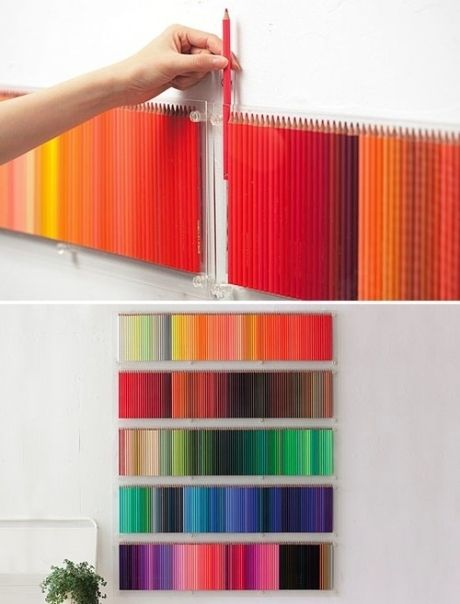 Colored pencils as art supply art.  Standing vertical behind  what looks like wall-mounted acrylic boxes with open tops.  Attractive and useful for an art studio.