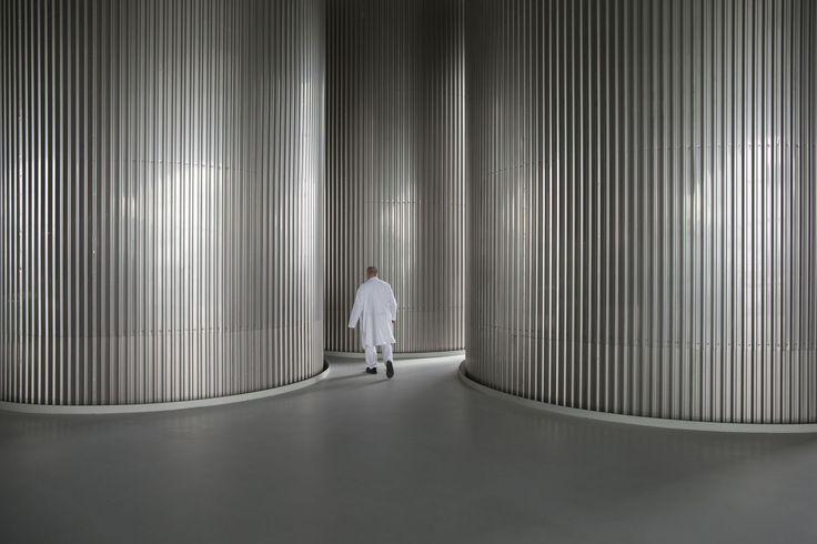 An employee passes between fermentation tanks inside the Grolsch beer brewery in Enschede, Netherlands. Photographer: Jasper Juinen/Bloomberg
