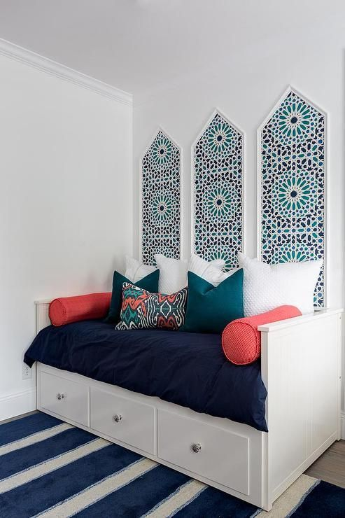 Chic kid's room boasts three black and teal wallpapered art panels placed above a white daybed fitted with three drawers dressed in navy bedding, peacock blue velvet pillows and pink bolster pillows atop a blue stripe rug.
