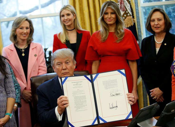 U.S. President Donald Trump holds up H.R. 321 as his daughter Ivanka Trump (C) and U.S. first lady Melania Trump (2nd R) watch after it was signed in the Oval Office of the White House, in Washington, DC, U.S. February 28, 2017. REUTERS/Joshua Roberts via @AOL_Lifestyle Read more: https://www.aol.com/article/news/2017/02/28/where-is-melania-trump-first-lady-finally-appears-at-white-house-after-absence/21859709/?a_dgi=aolshare_pinterest#fullscreen