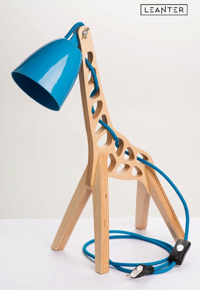 Voici une lampe de table en bois aux inspirations animales et plus particulièrement d'une girafe. Cette lampe designée par Leanter dispose d'un abat jour en métal coloré (orange, rouge, bleu, rose, noir, vert et jaune) et d'un câble d'alimentation qui contrastent avec le bois de la structure.