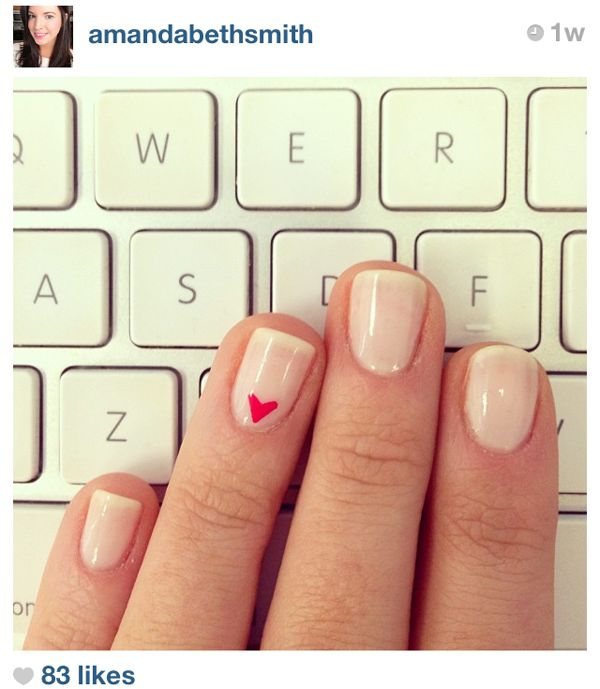 Simple heart nail polish on the ring finger of a plain nude