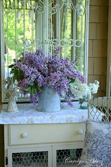 Beautiful explosion of lilacs in an old farm pitcher. I like the fabric there, to prevent a rust ring.