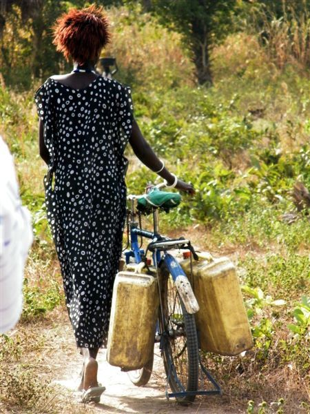 South Sudan woman pushes a bicycle with several water containers attached to it.