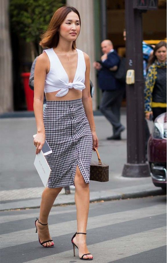 Nicole Warne of Gary Pepper Girl wears a tie-front crop top, gingham skirt, strappy sandals, and a Louis Vuitton bag