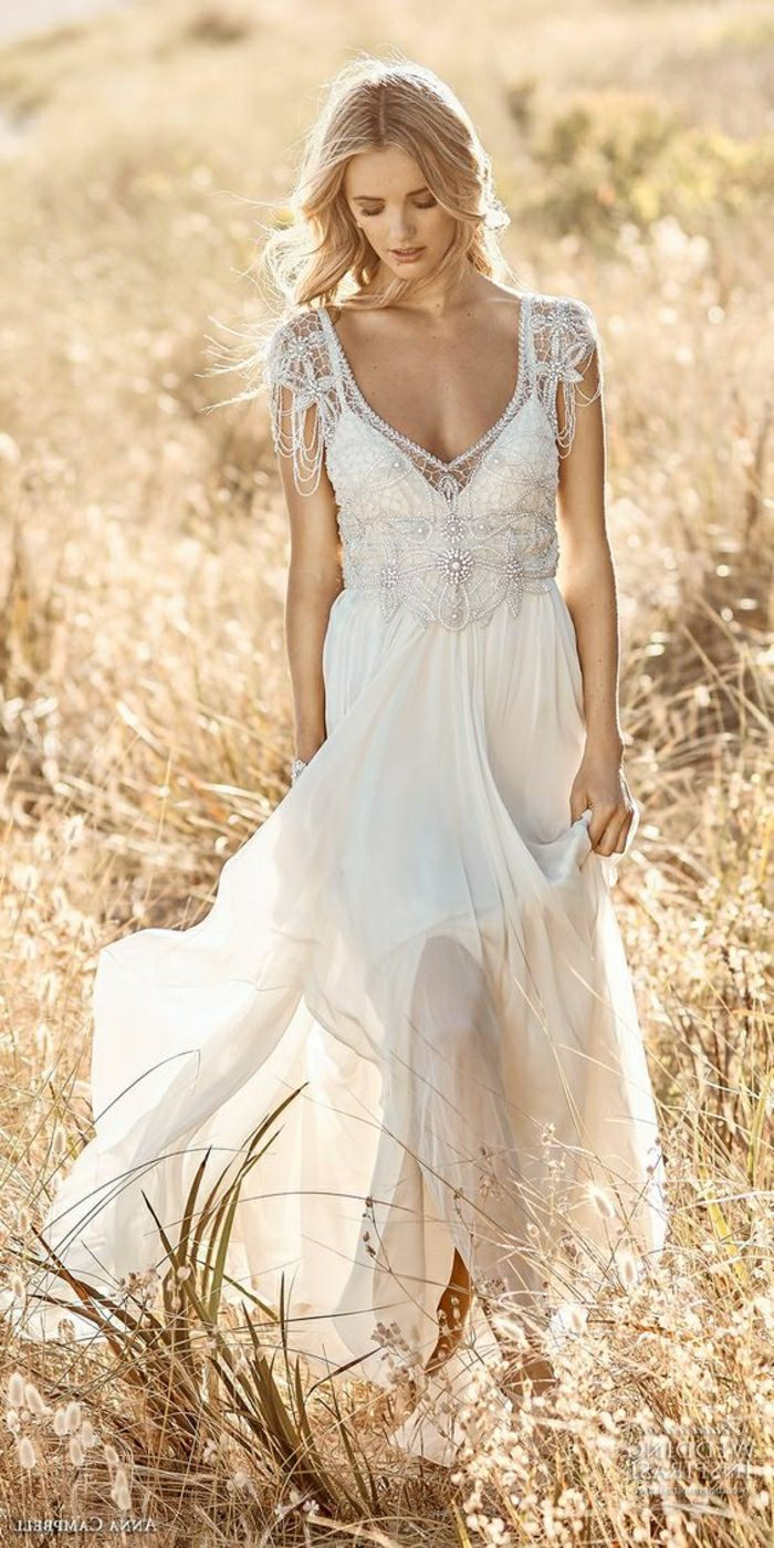 unique wedding dresses, blonde woman in long bridal dress with pearls and beads, holding her dress in one hand and walking through a yellow field looking down