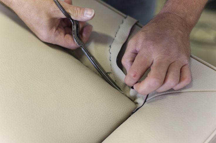 Le mani di chi taglia, cuce, sceglie, saggia la pelle, tasta i tessuti, verifica il legno massello, fissa molle e tiranti, infila bottoni.