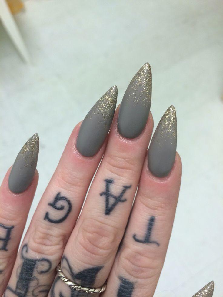 Matte gray with gold glitter stiletto nails. ✨