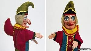 It wasn't until after 1825 that Punch transformed from a marionette into a glove puppet.     Mr. Punch has a very distinctive outfit: a jester's motley (a jester's jacket, similar to what a court jester would wear in medieval times) and a hat with a tassel. He carries his distinctive stick, called the 'slapstick,' used to beat other characters. He has a crooked nose & a hunchback.     Punch is created by carving his form out of wood. Other puppets can be made out of plaster molds & papier…