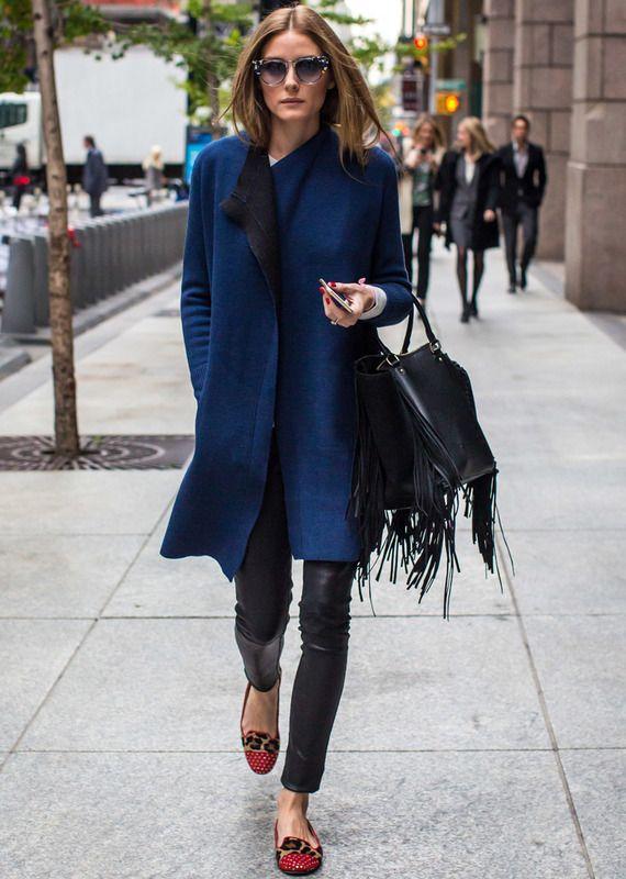 La reina del estilo y los looks de calle Olivia Palermo nos deja este look de calle con abrigo azul y negro, pantalones de piel, slippers rojos con tachuelas más animal print y bolso de flecos negro.