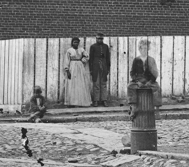 A black soldier stands with a woman and two children outside castle thunder a tobacco warehouse converted into a prison richmond va library of congress