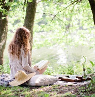 Manta de algodón, almohadón mullido y sombrero de paja para leer un libro y tomar té en el bosque. Relax total. Luz natural, pasto, pájaros y mucha belleza en Mar del las Pampas. Conocé Plenilunio.
