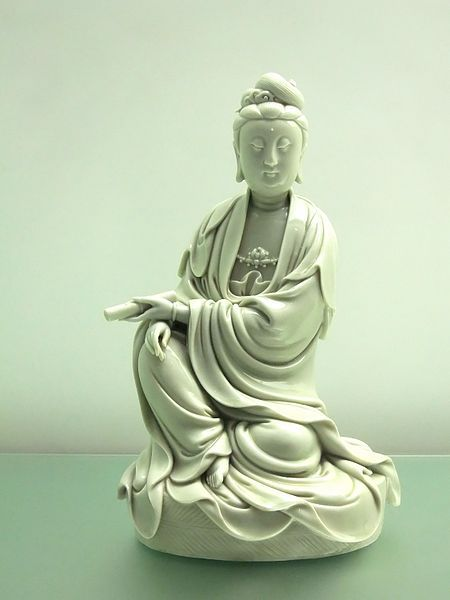 """Seated Guanyin in white glaze, Blanc de Chine (French for """"White from China"""", a type of white Chinese porcelain, made at Dehua in the Fujian province, otherwise known as Dehua porcelain). An exhibit on display at the Hong Kong Museum of Art"""