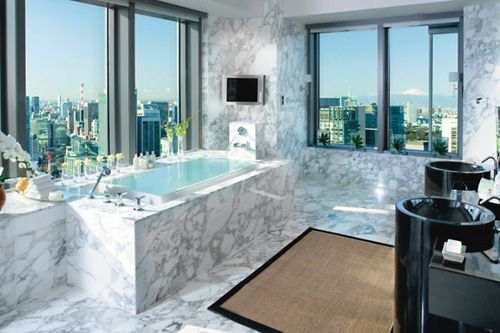 The Presidential Suite at Mandarin Oriental Tokyo has marbled bathroom features, a Jacuzzi bathtub, walk-in shower, black marble sinks, and a television. There are heated floors and towel racks, and plush terry bathrobes. The view from the tub includes a glimpse at Mount Fuji.