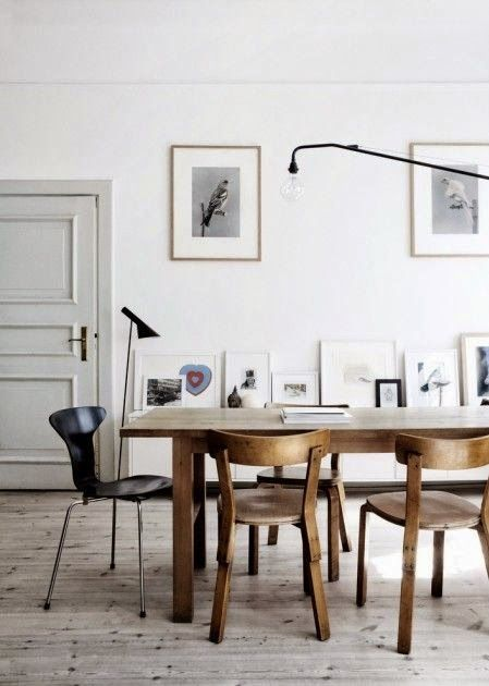 Rustic mix and match dining area with wall-propped art and bare wooden floors
