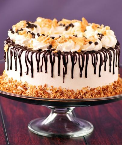 Moist gold cake laced with Myers Rum, filled with cannolie filling, frosted in whipped cream. Topped with drizzled chocolate ganache and whipped cream dollops sprinkled with crushed cannolie shells and chocolate chips and finished with caramelized nut sprinkles