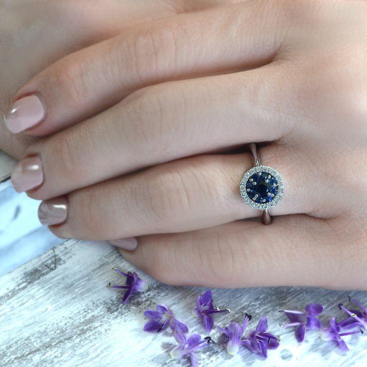 Anello con zaffiri e diamanti in oro bianco 18 kt, prodotto in Italia con manifattura interamente artigianale. Questo meraviglioso anello presenta uno zaffiro centrale circondato da piccoli zaffiri rotondi, che creano l'effetto di un unica pietra di dimensioni maggiori.