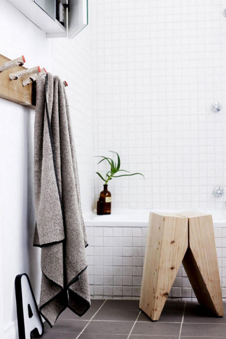 white bathroom grey floor tiles timber stool towel