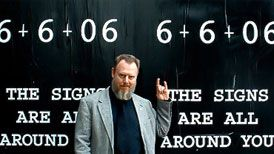 Magus Peter H. Gilmore in front of a poster for the 6.6.06 Satanic Ritual